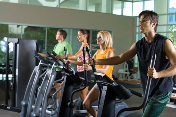 Homens e mulheres que usam uma máquina elíptica no ginásio